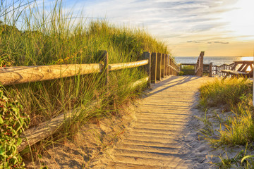 wooden path to the ocean. Ramp and wooden path to the sandy beach at sunset