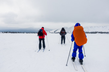 Caucasian people cross-country skiing in field