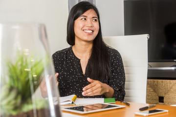 Smiling Asian woman gesturing in meeting