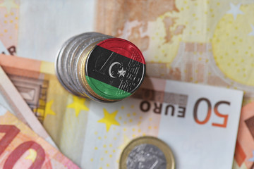 euro coin with national flag of libya on the euro money banknotes background.