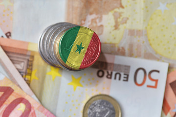 euro coin with national flag of senegal on the euro money banknotes background.