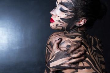 Разрисованная женщина задумчиво обнимает себя с закрытыми глазами.