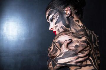 Разрисованная женщина крепко обнимает себя с закрытыми глазами.