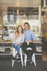 Smiling Caucasian couple sitting on stools outside coffee shop