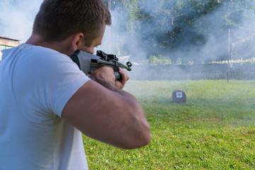 A man shoots a target from a pneumatic gun. Rear view of a man