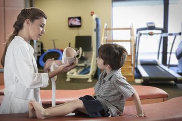 Caucasian doctor preparing cast for leg of boy