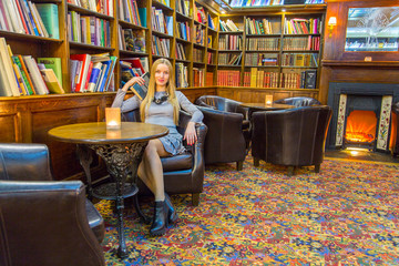 Beautiful girl sitting in a library combined with a pub