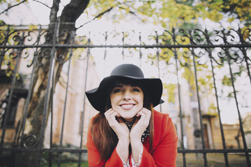 Portrait of smiling Caucasian woman wearing hat near fence
