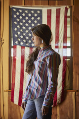 Portrait of serious Mixed Race teenage girl posing near American flag