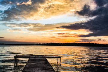 Sunset On Water / A boat dock in a large lake under orange and purple clouds at sunset.