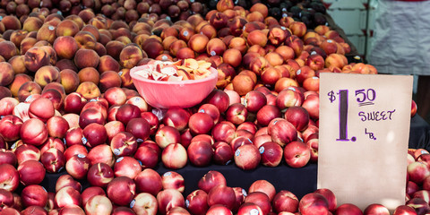 Piles of peaches and nectarines at a Farmers Market fruit stand. Bowl in center with samples of fruit to taste.