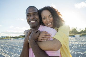 Portrait of smiling couple hugging on beach