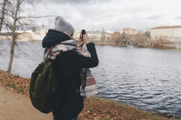 Caucasian woman photographing river with cell phone