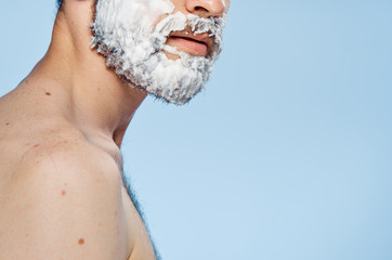 Man with a beard on a light blue background, portrait, shaving foam, empty space for copying