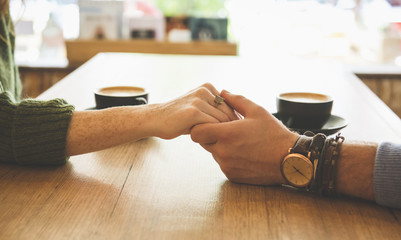 Close up of Caucasian couple holding hands in coffee shop