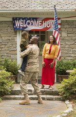 African American boy greeting returning soldier father