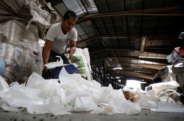 A worker selects plastic at a factory that produces plastic wood, posts and sheets with recycled plastic in San Jose