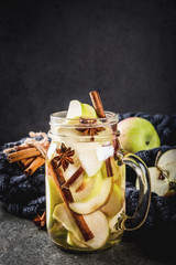 Autumn cocktail. Infused diet detox water with apples and spices - anise, cinnamon. Alcohol cocktail with apple cider. In mason jar on a black stone table. Copy space