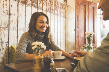 Smiling couple holding hands in coffee shop
