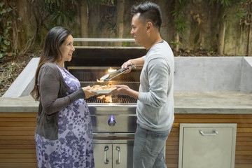 Man serving shrimp from grill to expectant mother