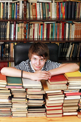 Boy with books in library