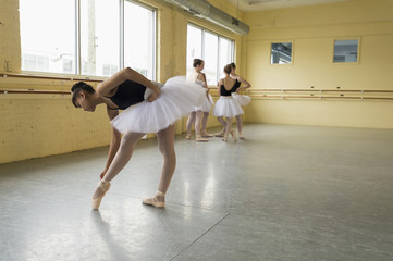 Girl checking shoe in ballet studio