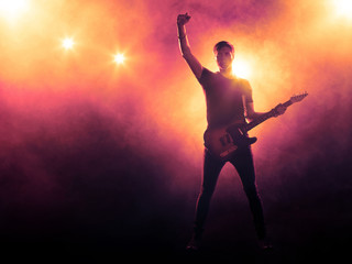 Silhouette of guitarist on stage on smoky background with spotlights Wall mural