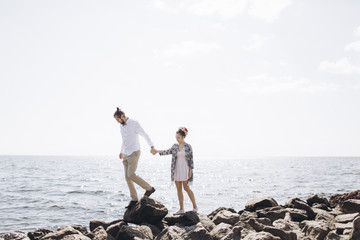 Middle Eastern couple walking on rocks near ocean