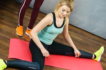 Woman in sportswear stretching legs