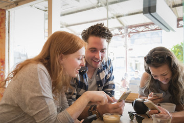 Friends texting on cell phones in coffee shop