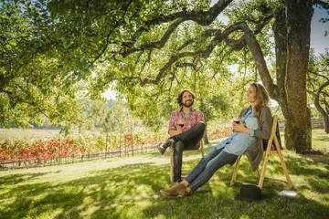 Hispanic couple drinking wine under tree