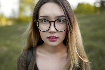 Asian teenage girl wearing eyeglasses in field
