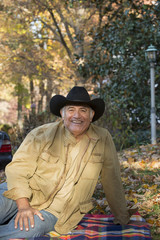 Portrait of Hispanic man sitting on blanket outdoors