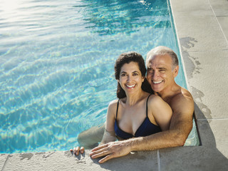 Portrait of older couple relaxing in swimming pool