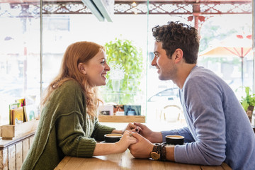 Caucasian couple holding hands in coffee shop