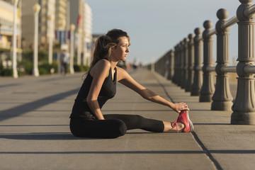 Caucasian teenage girl sitting on boardwalk stretching legs