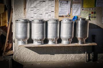 Old milk jar sitting on a bench in switzerland