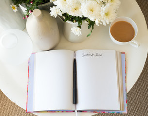 High angle view of blank gratitude journal with pen on desk with tea and flowers (selective focus)