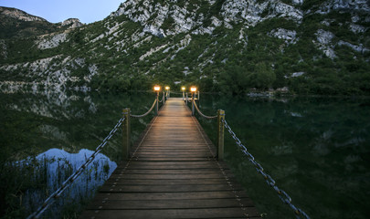 wooden bridge over a lake in the night