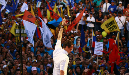 Opposition candidate Henrique Capriles waves to supporters during a campaign rally in Maracaibo