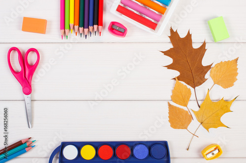 Frame of accessories for education and autumnal leaves on white ...