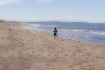 Young boy running fast down an empty beach beside glittering ocean waves in the sunlight