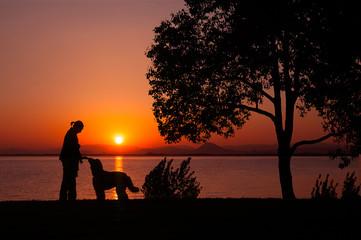 湖畔を散歩する女性と犬のシルエット