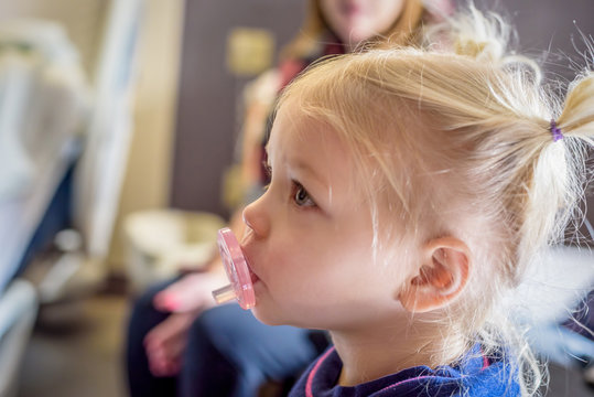Profile of little girl with pacifier and pigtails