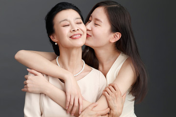Studio shot of young woman kissing mother
