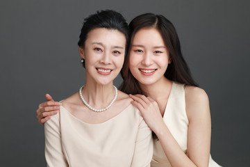 Studio portrait of woman with adult daughter