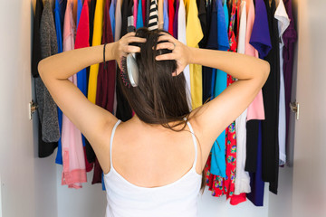 Frustrated woman standing in front of her closet, trying to find something to wear