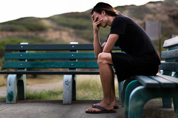 Young man sitting down depressed with his hands over face