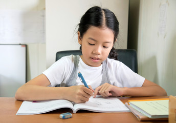 Happy young student Asian pre teens girl doing homework indoors at home countryside. Smart children drawing cartoon. Thai kid pay attention writing on book in house or school, education concept.