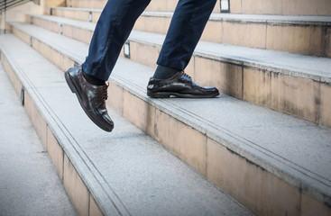 Close up legs of young Asian businessman walking upstairs outside office in the city , business concept copy space. Feet of traveling man in leather black shoes